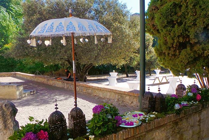 escenografía sombrilla clásica y muros de flores con lámparas