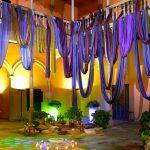 decoración de escenografía con telas moradas en patio andaluz